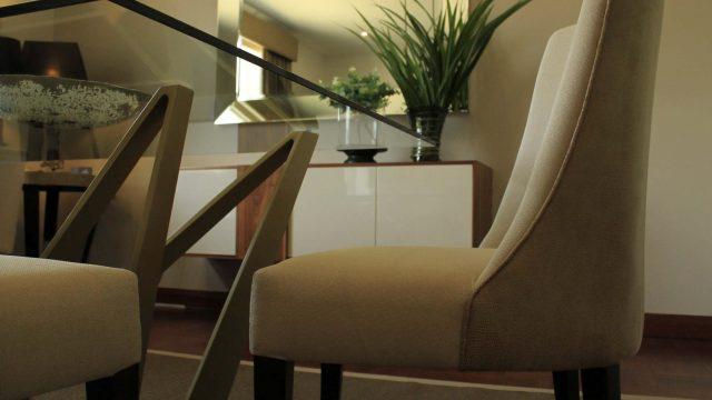 Base de mesa Monarca en fierro pintado y sillas Phillip con dos tonos de tapiz y patas en enchape importado acabado satinado