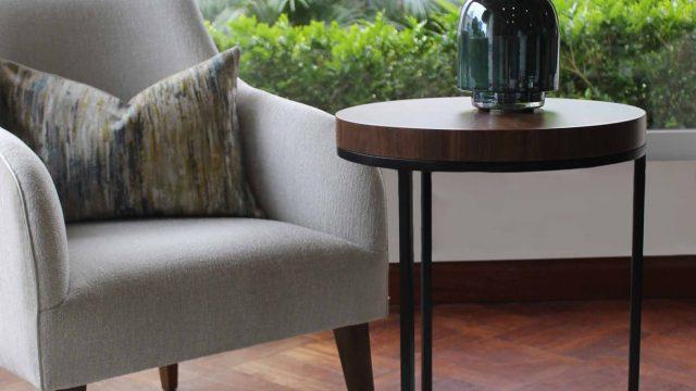 Butacas Mariella con patas en madera cedro acabado satiando y mesa auxiliar Lausanne con tablero con enchape de madera nogal americano y patas en fierro pintado