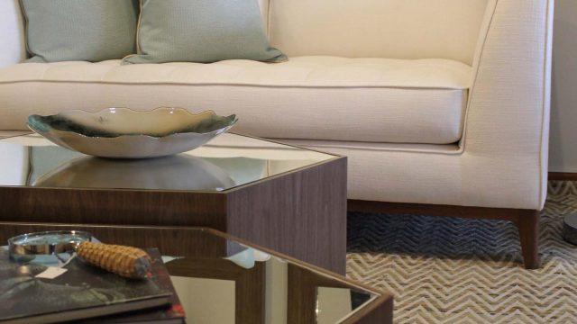 Mesa de centro Panal con tablero de espejo y cuerpo en madera enchapada en nogal francés y sofá Franco con patas en madera cedro